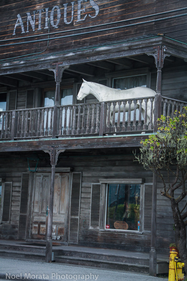 An antique store with a life size horse on the 2nd floor balconey