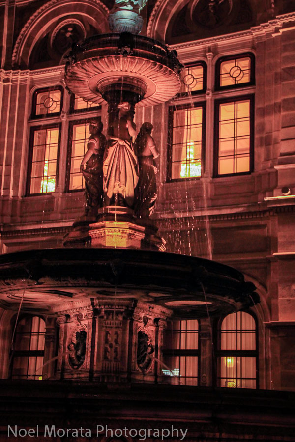 Lit fountain next to the Opera House of Vienna