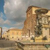 The colorful fountain and cathedral of Faenza
