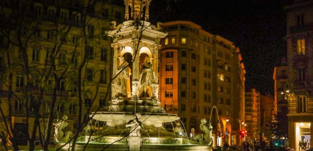 A lit fountain at night in Lyon, France at night time