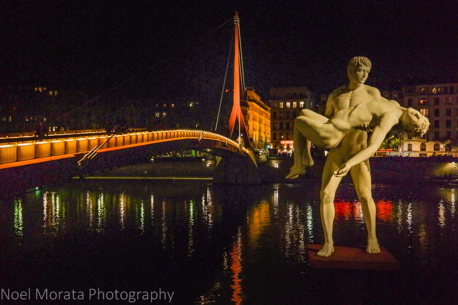 Drammatic sculpture at the Saone river, Lyon, France at night time