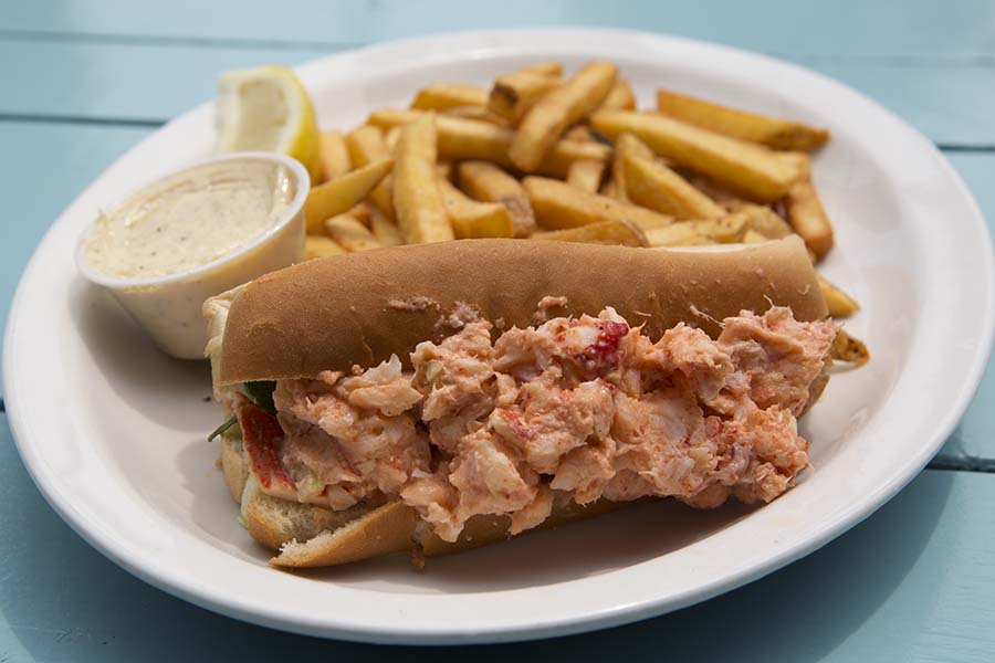 Lobster roll served with fries in Halifax, Canada. The dish is served with lemon and tartare sauce.